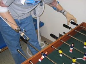 Um soldado demonstra como tecnologia avançada em prótese possibilitam continuar realizando atividades como jogar futebol de mesa (Totó). (Fonte: https://goo.gl/ZQpLvs)