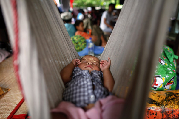 HIV-positive Ei Ei Phyu, who lives at the hospice with his HIV-positive mother, sleeps in a hammock at the HIV/AIDS hospice founded by a member of the National League for Democracy (NLD) party in the suburbs of Yangon May 26, 2012. Their plight demonstrates the painful limits of democracy in Myanmar. While the government is pursuing reforms that promise to overhaul its health ministry and other institutions, the process is too slow to bring change to its most destitute. There are few better examples than AIDS sufferers, who due to a combination of poor education, social stigma and bureaucratic mismanagement are isolated in clinics, cut off from society.  Picture taken May 26, 2012. To match Feature MYANMAR-HIV/  REUTERS/Damir Sagolj (MYANMAR - Tags: SOCIETY HEALTH) ATTENTION EDITORS PICTURE 09 OF 20 OF PACKAGE 'AIDS HOSPICE IN MYANMAR' TO FIND ALL IMAGES SEARCH 'MYANMAR HIV' - RTR32V28